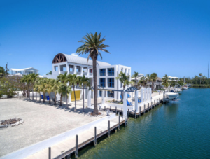 Picture of modern canal home with large glass windows. On a canal with seawalls, and boat lifts.